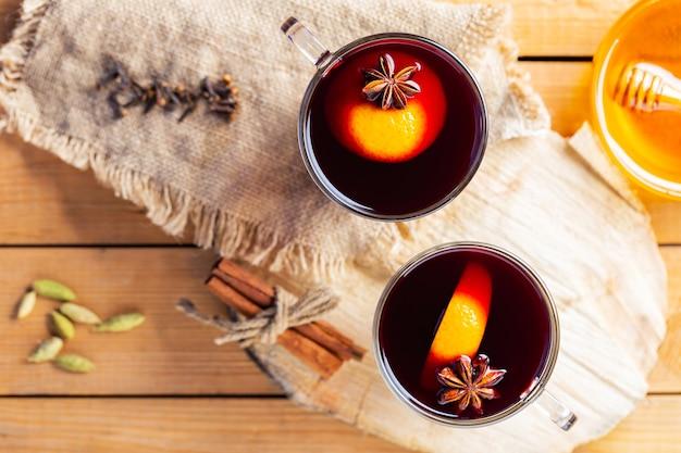Vinho quente em um fundo de madeira. vinho quente com especiarias e especiarias na serapilheira.