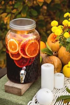 Vinho quente em uma lata de vidro em uma mesa festiva de outono para um jantar em família no jardim.