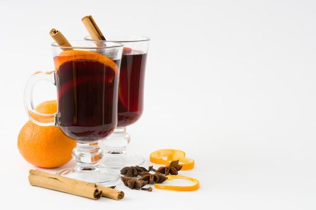 Vinho quente em vidro com especiarias e frutas isoladas no branco