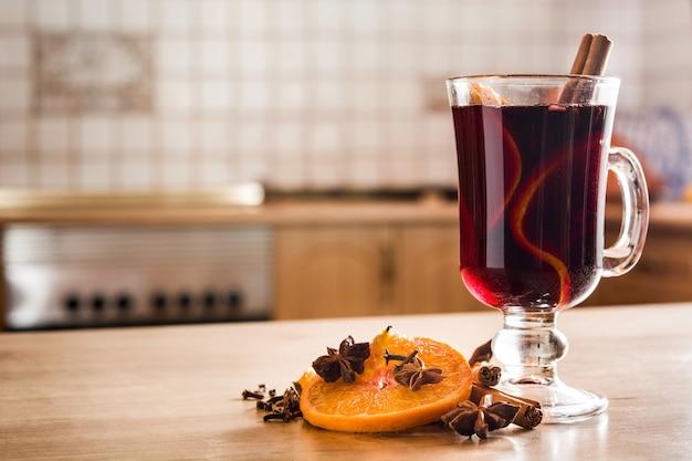 Vinho quente em vidro com especiarias e frutas na mesa de madeira copyspace