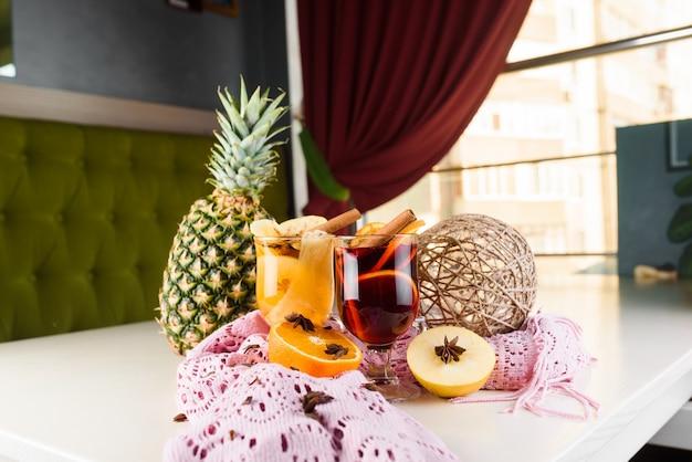 Vinho quente, grogue e ponche bebidas alcoólicas quentes em cima da mesa com decoração sazonal: abacaxi, canela, maçã, laranja, anis estrelado. bebida temperada sazonal.