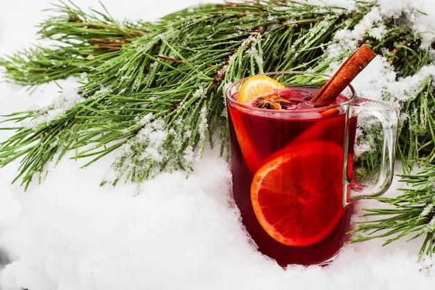Vinho quente na rua na neve com um ramo de pinheiro