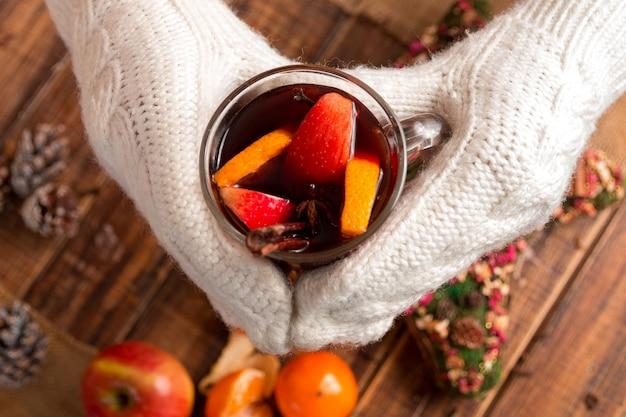 Vinho quente nas mãos de mulher em luvas de malha brancas perto de especiarias e ingredientes de frutas