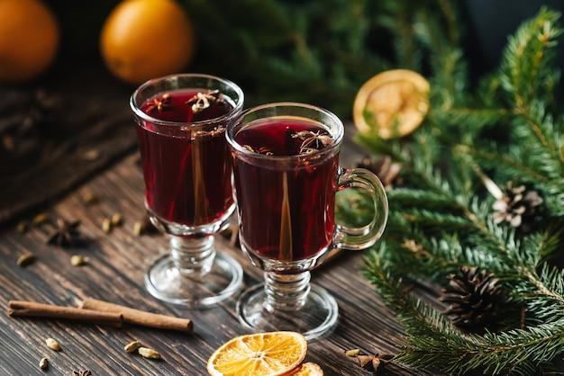 Vinho quente quente caseiro festivo com decoração de natal e especiarias em uma mesa de madeira
