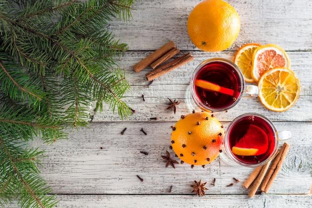 Vinho quente quente de natal com canela laranja e anis em fundo branco de madeira