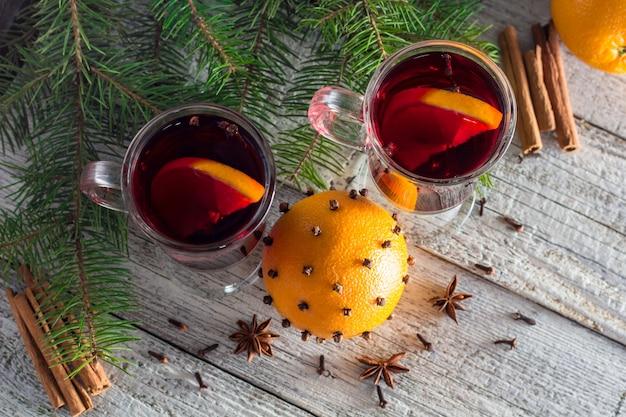 Vinho quente quente de natal com canela laranja e anis na superfície de madeira branca