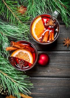 Vinho quente quente de natal com especiarias e ervas aromáticas. em uma madeira.