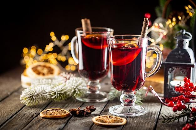 Vinho quente quente de natal com especiarias e frutas em fundo de madeira com luzes de natal