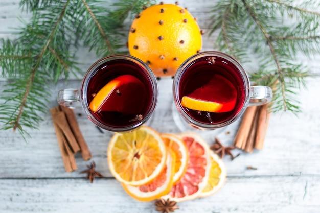 Vinho quente quente de natal com laranja e canela e anis em fundo branco de madeira com árvore