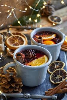 Vinho quente quente de natal em duas canecas rústicas com frutas e especiarias