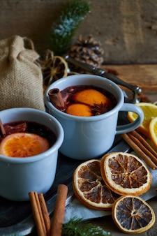 Vinho quente quente em canecas de metal cinza com laranja e especiarias estilo rústico