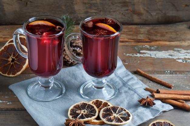 Vinho quente quente em dois copos com frutas e especiarias na mesa de madeira