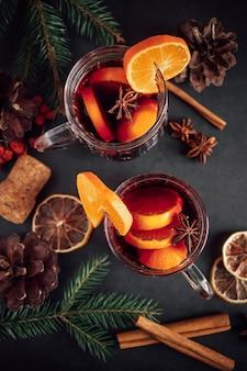 Vinho quente quente tradicional de natal. bebida quente com especiarias em copo de vidro em um fundo escuro.