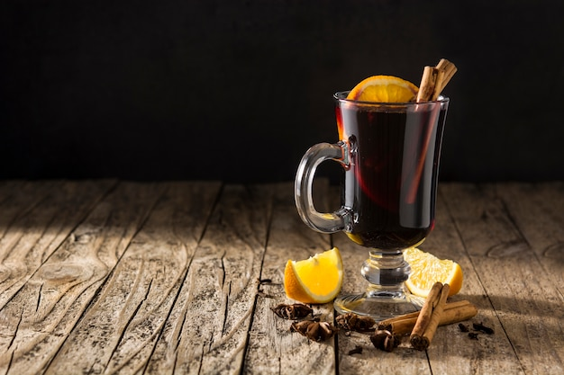 Vinho quente tradicional com especiarias na mesa de madeira