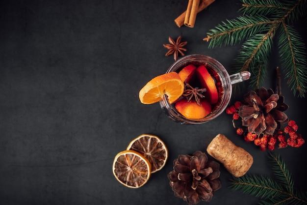 Vinho quente tradicional de natal. bebida quente com especiarias em copo de vidro em um fundo escuro.