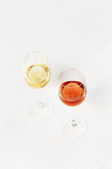 Vinho rosa e branco em vidro na mesa de madeira clara bar de vinhos, adega, conceito de degustação.