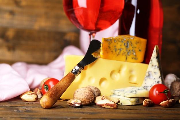 Vinho rosa e diferentes tipos de queijo em fundo de madeira