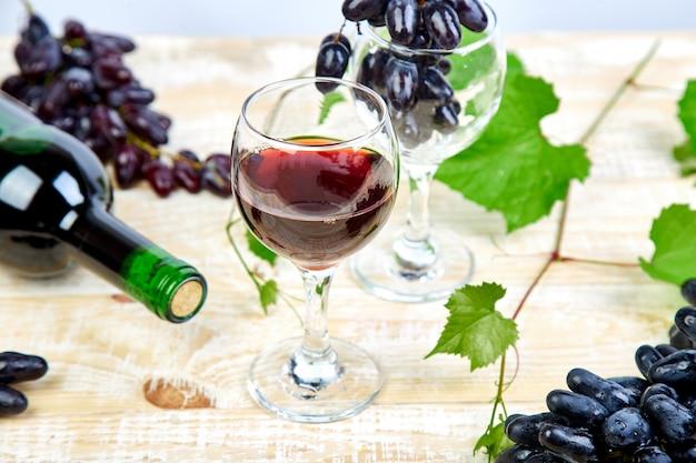 Vinho tinto com garrafa, copo e uvas.