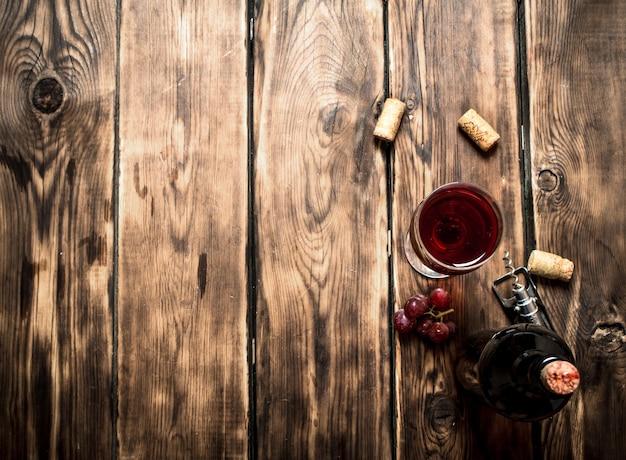 Vinho tinto com rolhas na mesa de madeira.