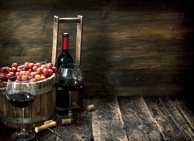 Vinho tinto com um balde de uvas na mesa de madeira.