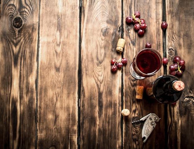 Vinho tinto com um ramo de uvas e um saca-rolhas. em uma mesa de madeira.
