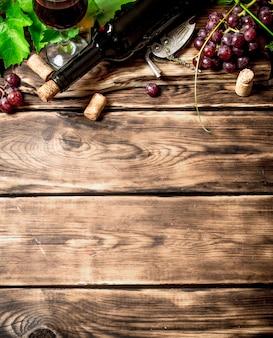 Vinho tinto com um ramo de videira. em uma mesa de madeira.
