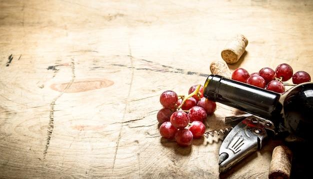 Vinho tinto com um saca-rolhas, uvas e rolhas na mesa de madeira.