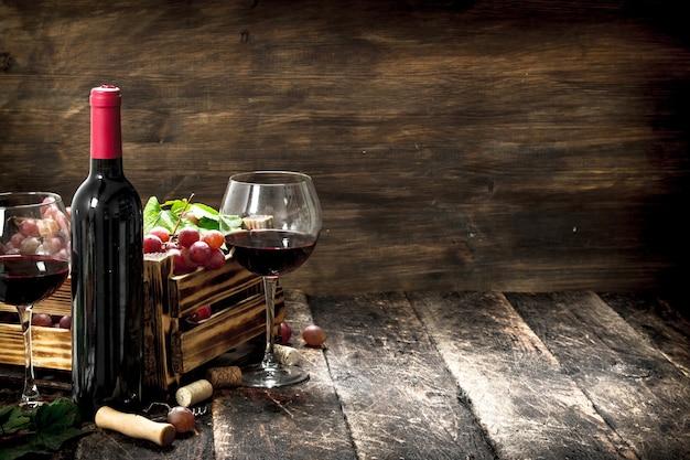 Vinho tinto com uma caixa de uvas na mesa de madeira.