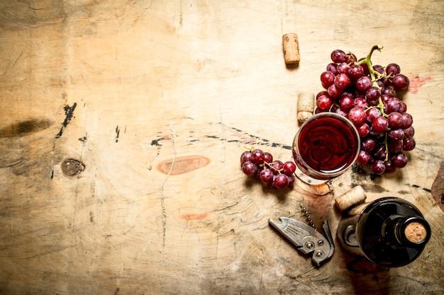 Vinho tinto com uvas e rolhas na mesa de madeira.