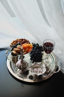 Vinho tinto, copo de vinho com nozes, uvas e figos em fundo escuro