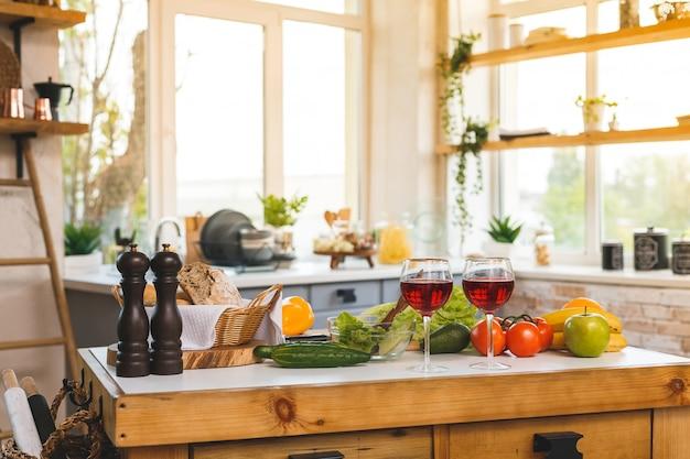 Vinho tinto, copos e comida saudável em uma mesa na cozinha moderna. interior de casa.