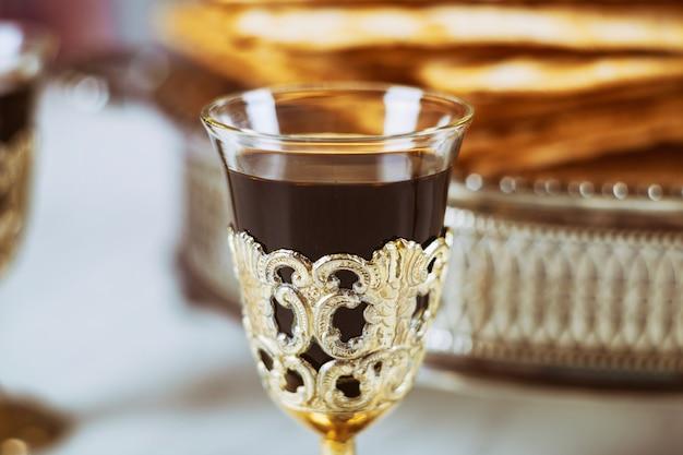 Vinho tinto do fundo da páscoa judaica e pão judaico do feriado do matzoh sobre a placa de madeira.