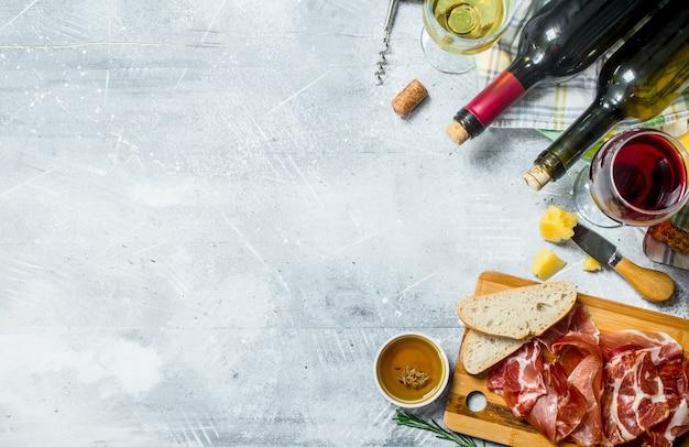 Vinho tinto e branco com petiscos de carnes e queijos em uma mesa rústica.