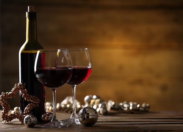 Vinho tinto e enfeites de natal na mesa de madeira com fundo de madeira