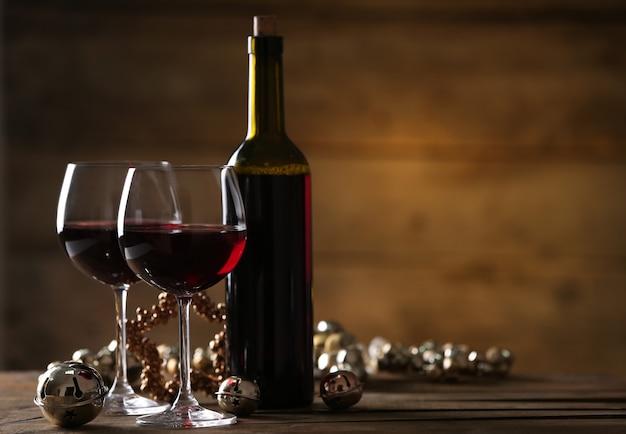 Vinho tinto e enfeites de natal na mesa de madeira na superfície de madeira