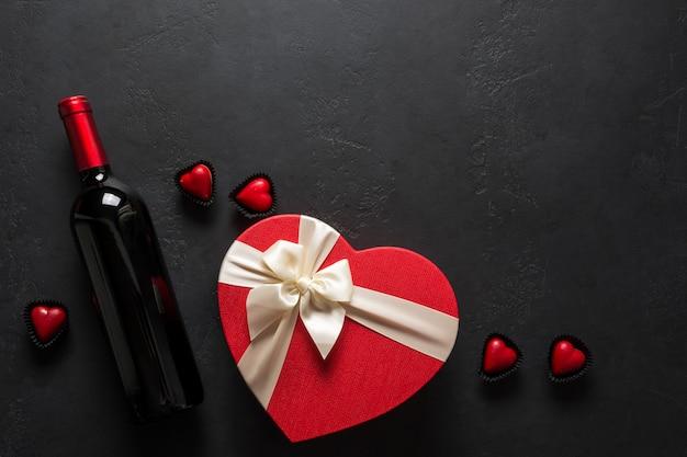 Vinho tinto e presente em forma de coração em fundo preto. cartão romântico de dia dos namorados. vista de cima. espaço para texto.