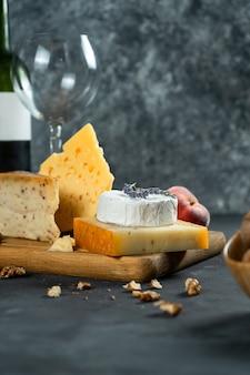 Vinho tinto e queijo. diferentes tipos de queijo com nozes, alfazema e figo pêssego na tábua. jantar romântico. copie o espaço para o projeto. fundo escuro. foco suave