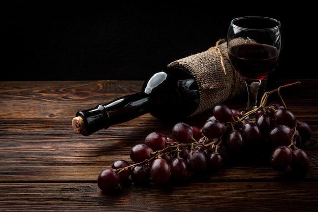 Vinho tinto e uva no fundo escuro de madeira.