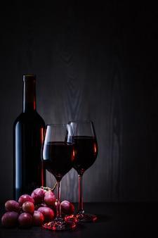 Vinho tinto em copos e garrafa com cacho de uvas vermelhas