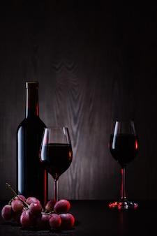 Vinho tinto em copos e garrafa com cacho de uvas