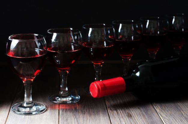 Vinho tinto em copos e garrafa de vinho.