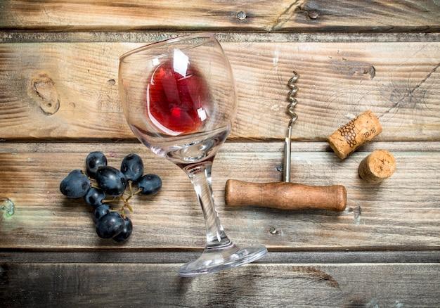 Vinho tinto em um copo com uvas e um saca-rolhas. em uma mesa de madeira.