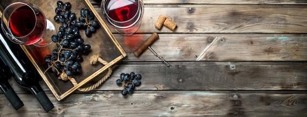 Vinho tinto em um copo com uvas e um saca-rolhas. sobre um fundo de madeira.