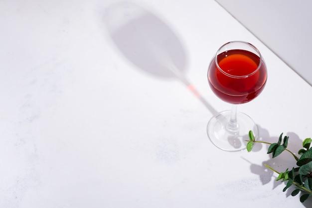Vinho tinto em um copo de vinho com sombras isoladas no fundo de pedra branco