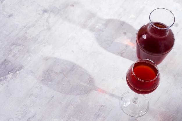 Vinho tinto em um copo de vinho e jarra com sombras isoladas no fundo de pedra branco