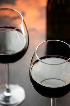 Vinho tinto em um vidro, close-up, foco seletivo. uma garrafa de vinho tinto e dois copos em cima da mesa. vertical