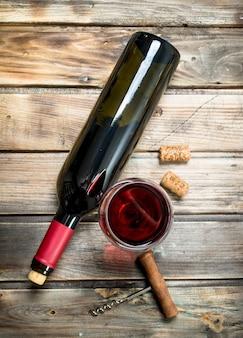 Vinho tinto em uma taça de vinho com um saca-rolhas. em uma madeira.