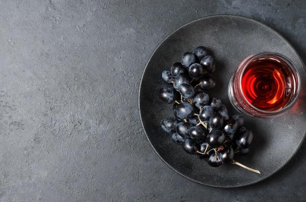 Vinho tinto em vidro com um cacho de uvas pretas