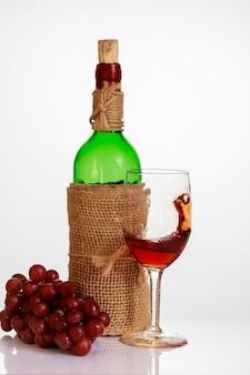 Vinho tinto em vidro com uvas e garrafa em fundo branco.