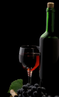 Vinho tinto em vidro e garrafa isolada em fundo preto